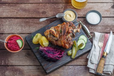 Roasted pork knuckle on black wooden board with appetizer and beer, copy space