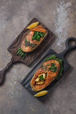 Two salmon steaks with vegetables on wooden boards, copy space