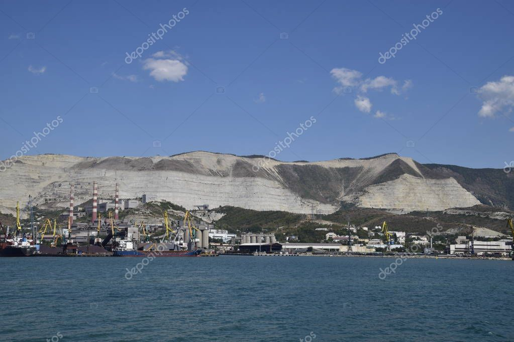 international seaports. Cargo port with port cranes. Sea bay and mountainous coast.