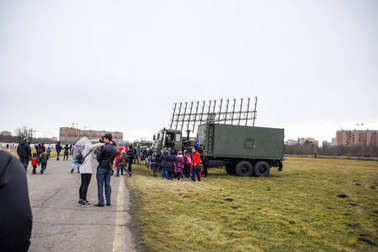 Exhibition of military equipment at the Krasnodar airfield. Viewers inspect Military cars and a mobile radar station.