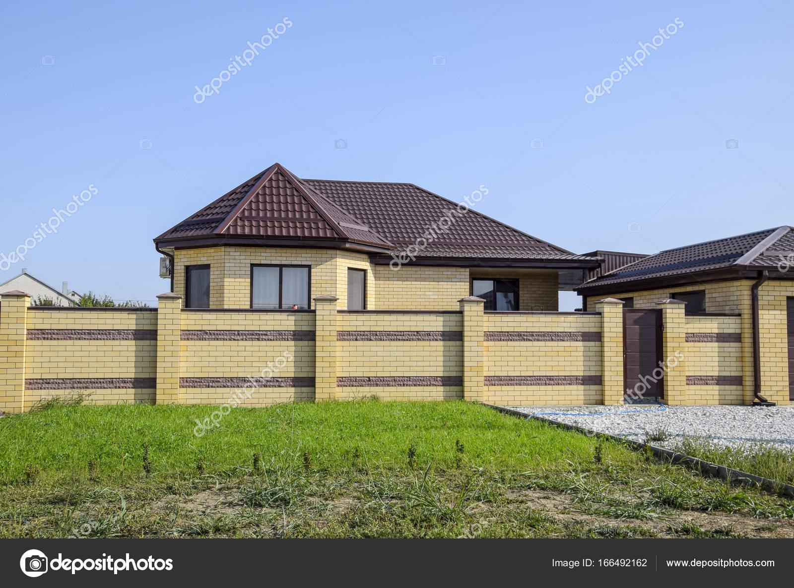Maison en brique avec une cl ture et portails vue d une for Prix maison en brique