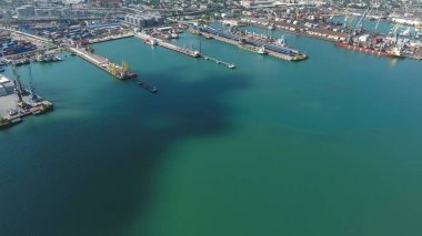 Industrial seaport, top view. Port cranes and cargo ships and barges.