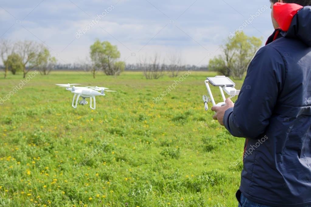 Field next to Krasnodar, Russia - April 15, 2017: A man with a remote control in his hands. Flight control of the drone. Phantom.