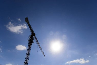 Tower building crane against the blue sky and sun. Construction of new buildings with a crane. Tower crane.