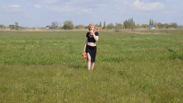 Krásná dívka v černých šatech je spuštěn s červenými tulipány ve svých rukou.