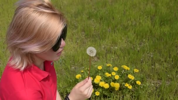 Krásná blonďatá dívka foukání pampeliška. Semínka pampelišky jsou foukané pryč od dívka. Jarní kvetoucí Pampeliška.