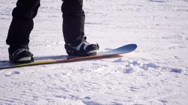 Zeitlupe aus nächster Nähe: Snowboarder fahren und springen auf Skipiste in verschneiten Bergen