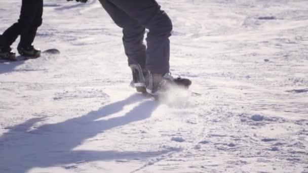 Zpomalený pohyb zblízka: Snowboardista na koni a skákat na sjezdovce v zasněžených horách