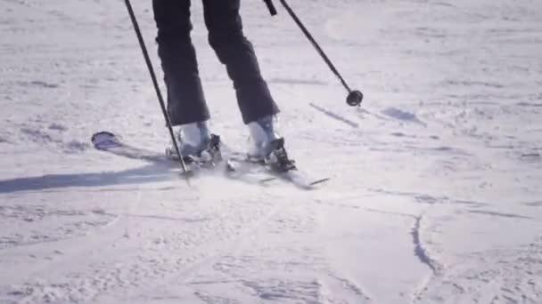 4k Rückansicht eines professionellen Skifahrers, der den schneebedeckten Hang hinunter carvt