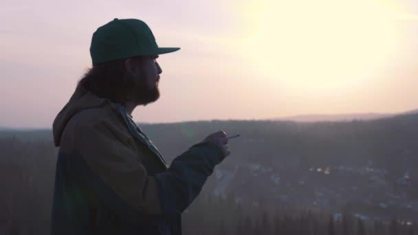 Portrét osamělého muže, kouří cigaretu při západu slunce. Muž kouří cigaretu