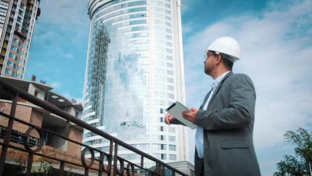 Adult engineer or architect uses a tablet in operation. Writes a message or checks a drawing. Against background is building. Builders are building a modern residential building of glass and concrete