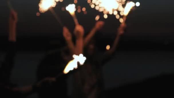 Visszapillantó a barátok együtt fut a gazdaság csillogó tűzijáték strandon. barátnő barátnője futni a parton, az este vagy éjszaka