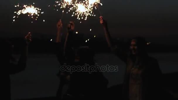 Zpětná přátelé běží spolu na pláži drží šumivé ohňostroj. přítelkyně přítelkyně běžet podél pobřeží, večer nebo v noci