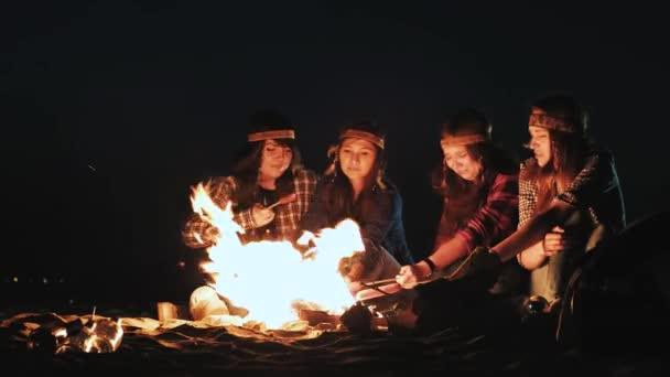 několik děvčat sedí u ohně v noci a osmahneme klobásy. Diskutovat a vést konverzaci. O kampani