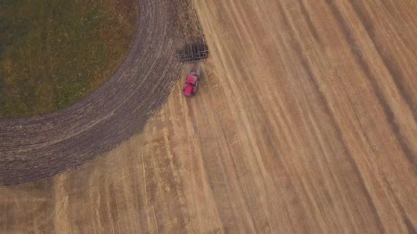 Anténa: Střelba na dron nad polem orné půdy. Červený traktor vymaže pole na podzim