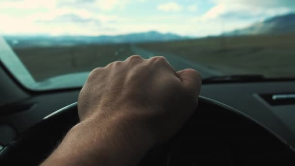Man driving his car. Driving car at holiday, nature. Male Hand on steering wheel closeup. Goes on the highway. You can see the mountains ahead. Travelling by car.