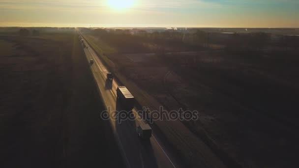 Anténa: Dodávky nákladních automobilů jízdy směrem ke slunci. auto s kontejnerem jezdí na cestě do západu slunce. Kamion jede po dálnici