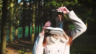The girl uses virtual reality glasses in the park or in the woods. Playing the game 360 degrees.