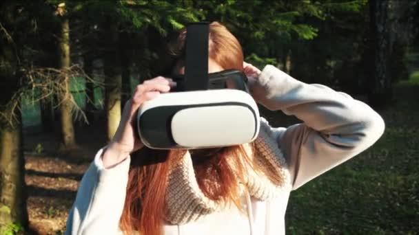 a lány használja a virtuális valóság szemüveg a parkban, vagy az erdőben. A játék 360 fok