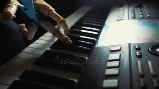 Robota hraje na hudební nástroj. muž hudebník pianista s protézou hraje na klavír. On si hraje s oběma rukama, ruce robota a lidská ruka. Robot vytváří hudbu a umění