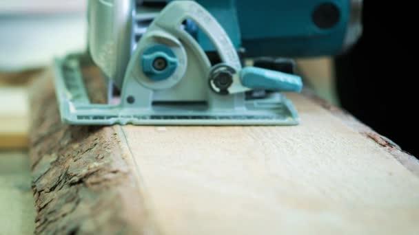 Řezací dřevěnou podlahu elektrická řetězová pila. Carpenter pily protokol nebo desky.