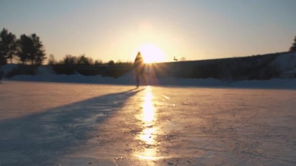 Close Up, nízký úhel pohledu: Eva šťastná žena rychle na zamrzlé v místním parku Zlatý západ slunce na kouzelné vánoční večer. Lidé na brusle užívat zimních aktivit v přírodě, baví
