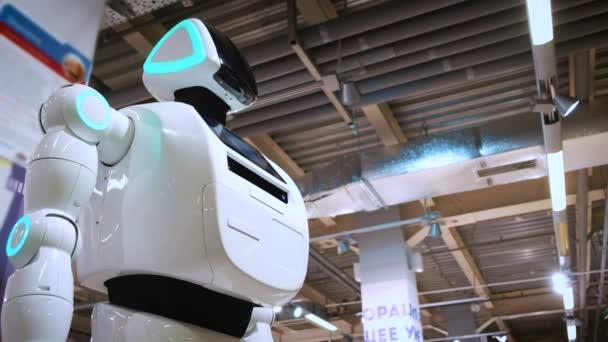 Portrét nového moderního bílého robota. Robot natáčí hlavu, hledí do kamery. Výstava robotů a robotických technologií vysoké
