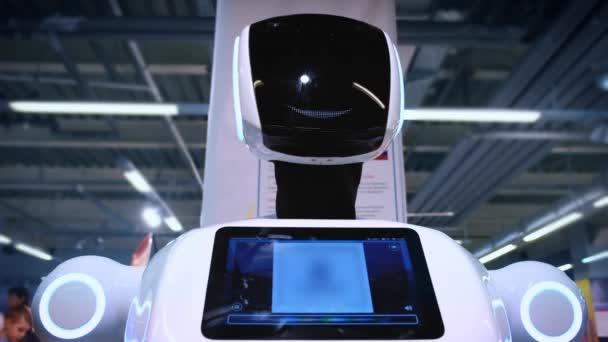 Egy új, modern fehér robot portréja. A robot fordul a fejét, néz a kamerába. Kiállítás a robotok és a magas robot technológiák