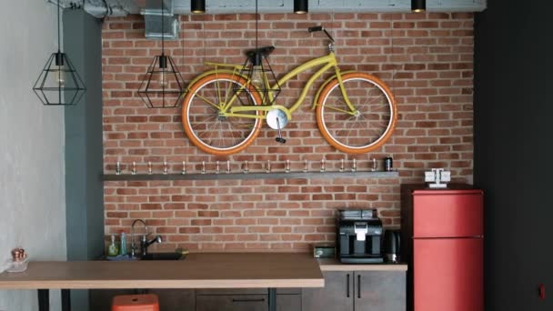 moderní interiér ve stylu podkroví. V kuchyni je bar, lednice a dekorativní kolo