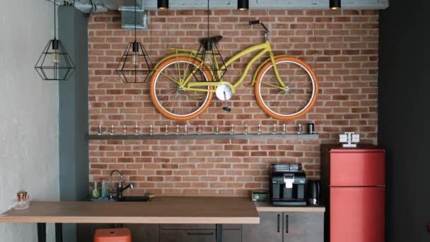 moderní interiér ve stylu podkroví. V kuchyni je bar, lednice a dekorativní kolo.