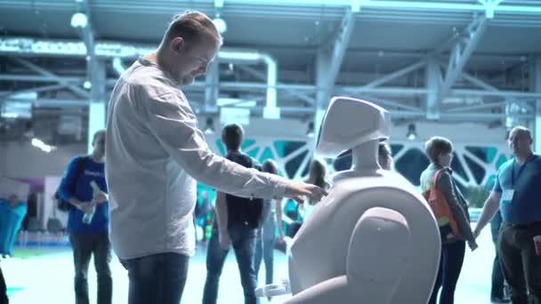 Moderní robotická technologie. Muž komunikuje s robotem, stiskne plastové mechanické rameno robota, handshake.
