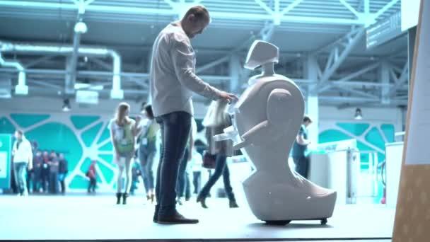 Robotika modern technológia. Egy ember kommunikál egy robot, megnyomja a robot egy műanyag mechanikus kar kézfogás.
