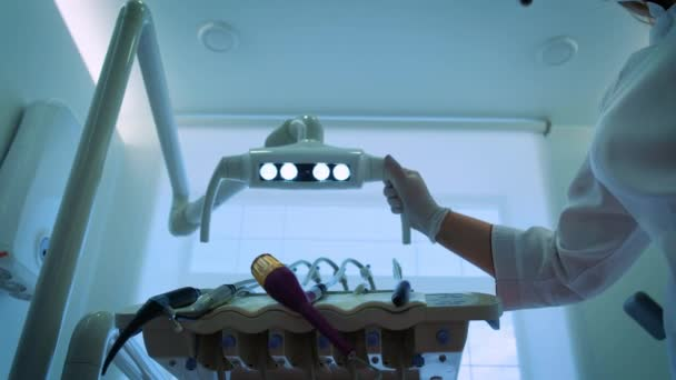 two doctors of the dentist in Mask is Smiling, Holding a Mouth Mirror and Hook, Turns the Light of Dental Lamp On, Lights Into a Patients Mouth, Standing Upon a Patient, Looking at Camera,trying