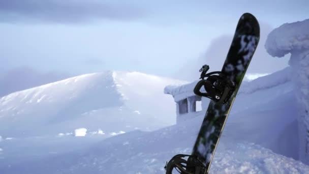 Snowboard steht im Schnee. stecken in einer Schneewehe vor der Kulisse eines Gebirges fest. Schneebedeckte Winterberge im Norden, hibiny. Abendlandschaft jenseits des Polarkreises.