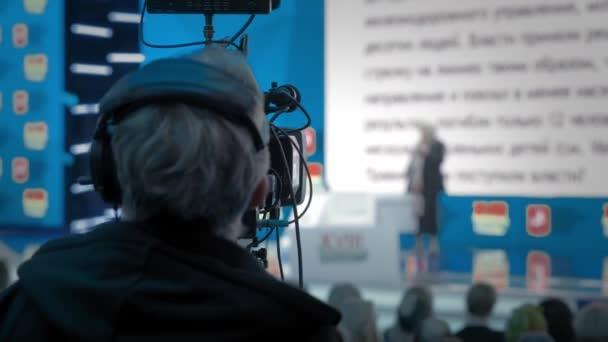 Der Kameramann macht Videos für das Fernsehen. Auditorium, Seminar und Vortrag über Wirtschaft. Berufsideen, Politik oder Wirtschaft. Energie gestikulierend im großen Raum.