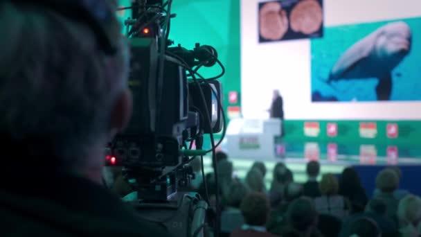 Der Kameramann macht Videos für das Fernsehen. Auditorium, Seminar und Vorlesung über Wirtschaft.. Videokamera zeichnet die Leistung des Vortragenden im Präsentationssaal auf
