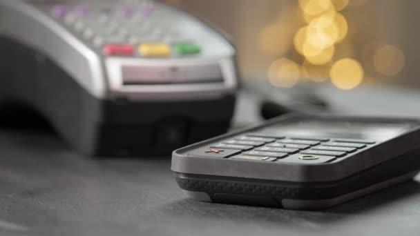 NFC technológia. Közelkép egy fiatal nőről, aki NFC chipet használ a bankterminálon. Vásárló fizet a kültéri ételrendelésért. Az érintésmentes hitelkártyával fizető ügyfélkezek részletei.