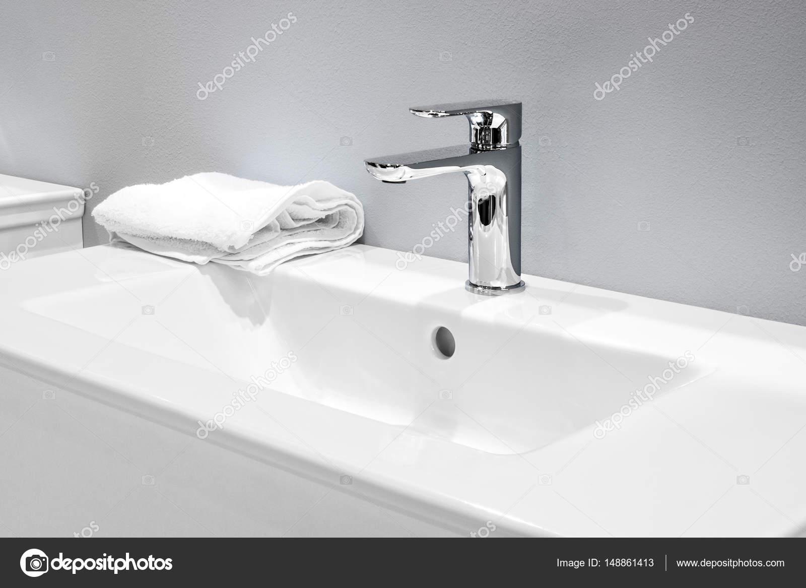 Luxe mixer op een witte wastafel in een mooie grijze badkamer