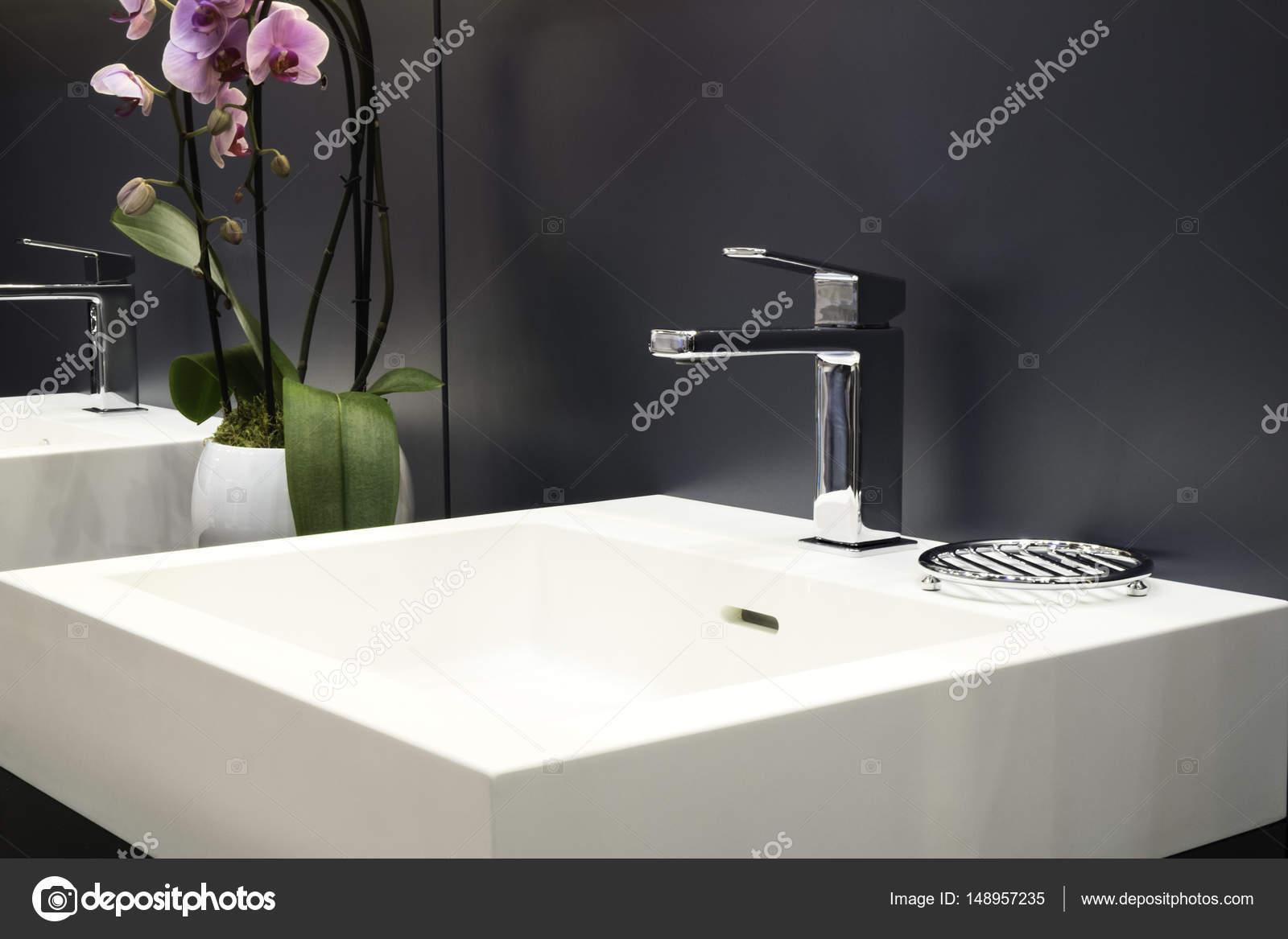Luxe kraan mixer op een witte wastafel in een mooie grijze badkamer