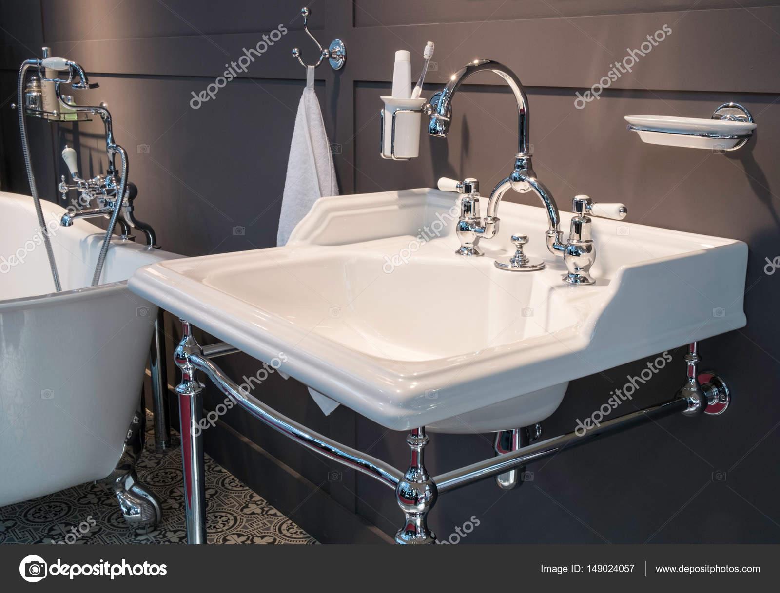 Luxe Donkere Badkamer : Luxe kraan mixer met witte keramische grepen op een witte wastafel