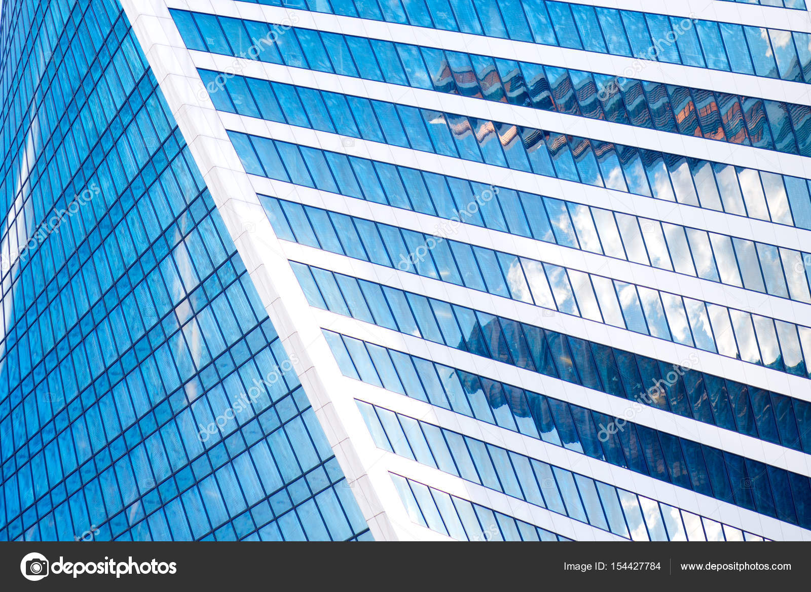 abstract skyscrapers with reflection in windows blue sky white