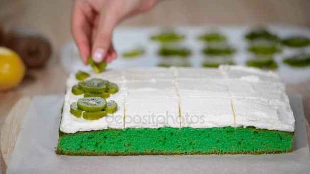 Dort zdobení. Detailní záběr z cukrář pekař ruce zdobí dort s kiwi ovoce