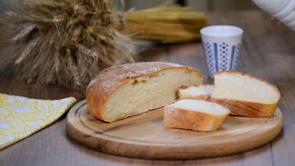 Domácí chléb, mléko a zralé klasy žita na dřevěné pozadí.