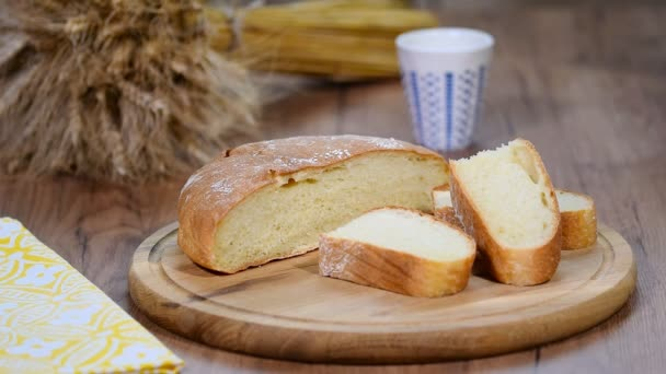 Homemade bread, milk and ripe ears of rye on a wooden background