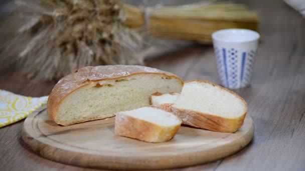 Házi kenyér, a tej és a érett fül rozs egy fából készült háttér