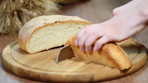 Férfi kezét vágás zeke búza kenyér a fából készült táblán