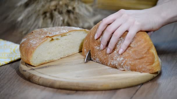 Woman cutting bread on wooden board. Bakehouse. Bread production