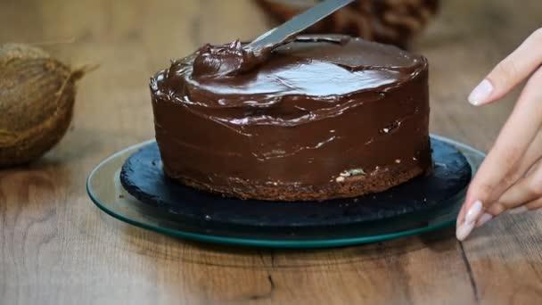 Cukrář, pokrývající dort s čokoládovou smetanou