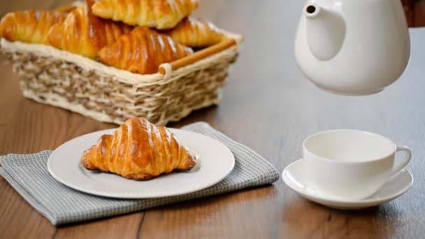 Croissant with tea. Breakfast concept. Pouring tea into cup of tea