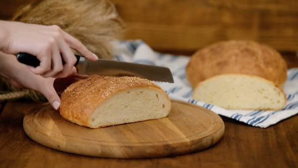 Žena, řezání chleba na dřevěné desce. Pekárna. Výroba chleba.